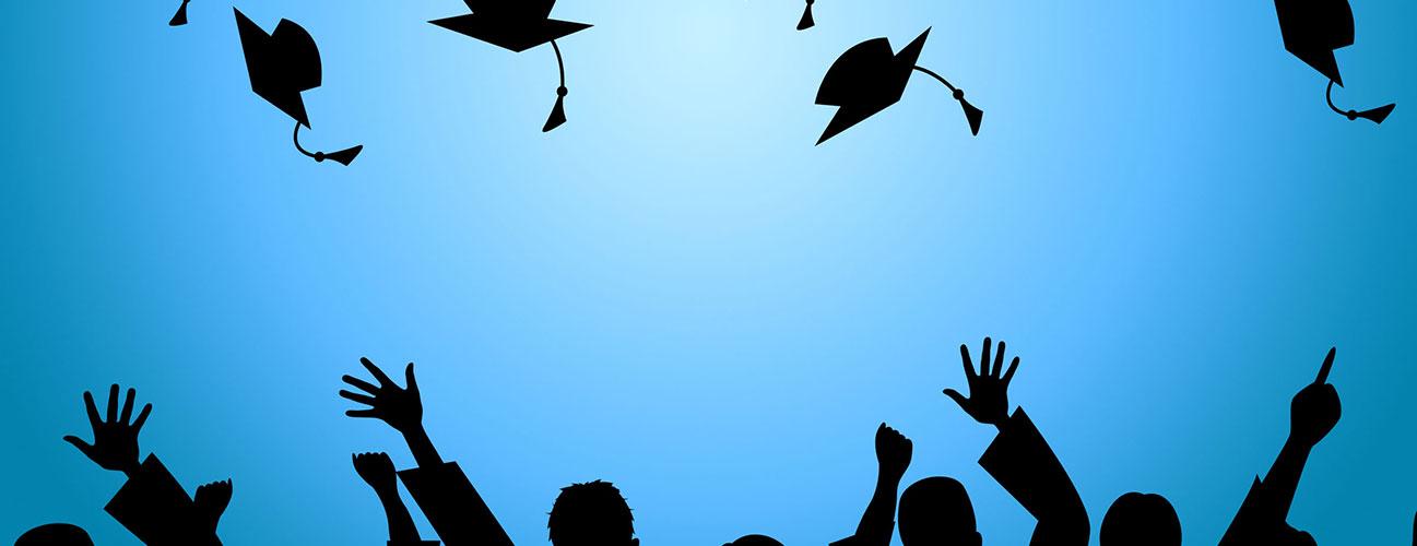 graduates throwing graduation cap in the air